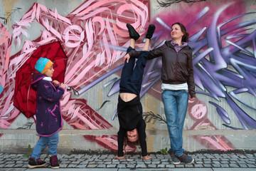 Glückliche Mutter mit Kindern Handstand vor Graffiti Fassade