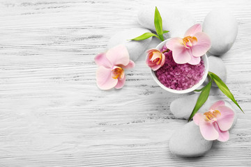 Spa stones, sea salt and orchid flowers on wooden background