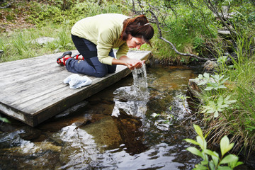 Woman drinking water from stream