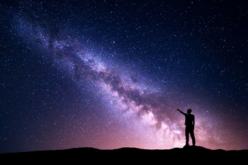 Milky Way with silhouette of a standing young man pointing finger in night starry sky on the mountain. Night landscape. Beautiful Universe, travel background with purple sky full of stars and light