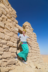 Tourist with turban posing in front of ruined stone house in desert, Egypt.