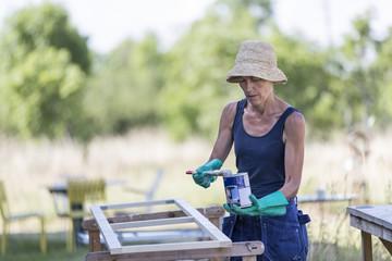 Mature woman painting window