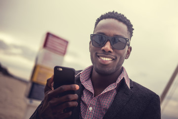 Portrait of smiling afro american male with smartphone.