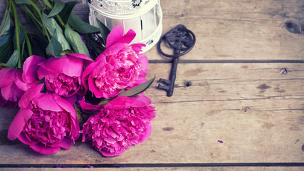 Pink peonies flowers on aged wooden background.