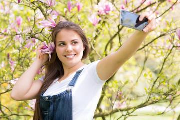 junge frau fotografiert mit dem mobiltelefon ein selfie