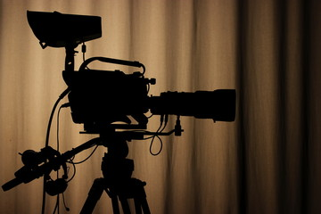 Silhouette of professional tv camera on a brown background