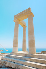 Famous Greek temple three pillars against clear blue sky and sea in Lindos Acropolis Rhodes Athena Temple, Greece