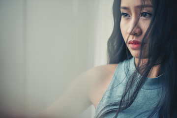 Portrait of pensive unsmiling Vietnamese woman at window