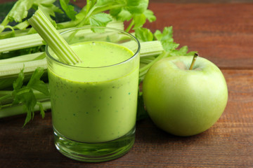 Fresh green celery juice in glass near green Apple on the brown wooden background