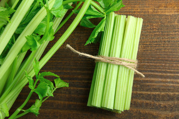 Fresh green celery wrapped with a rope on a brown wooden background