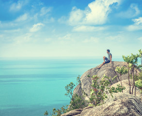 One man sits on a hill with stunning sea views