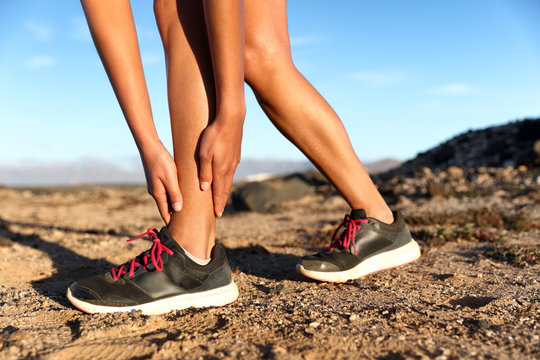Runner woman with hurt ankles in pain during marathon. Athlete woman running outside with body injury. Sprained ankle on trail run in summer outdoors nature. Fitness leg accident on cardio workout.