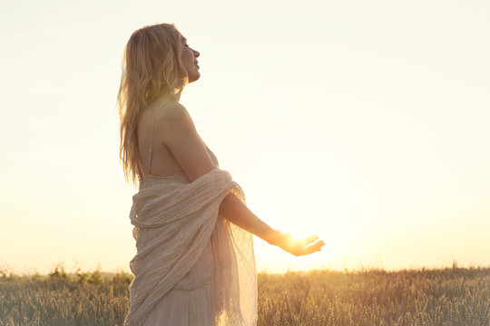 romantic woman holding the sun in hand
