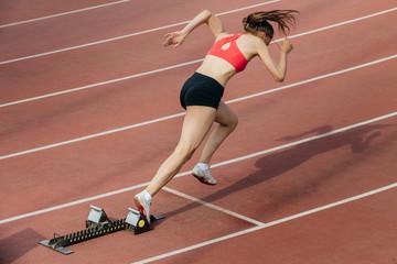 woman sprinter at start of 400 metres at stadium