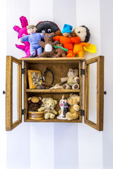 Old rustic wall mounted wood display cabinet stuffed with items and toys.