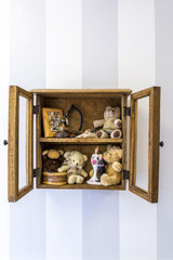 Old rustic wall mounted wood display cabinet stuffed with items and toys, vertical.