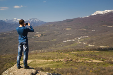 man standing on a cliff and making photo