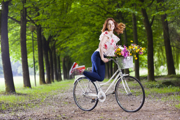 Young woman holding a vintage bicycle and jumping at the park