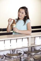 Girl Having Chocolate Ice Cream At Counter