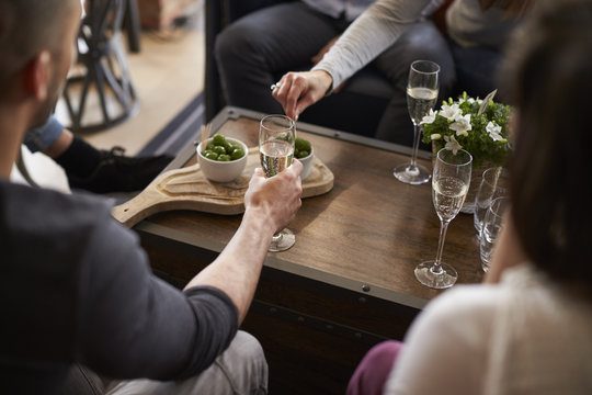 Group of friends celebrating with champagne in bar