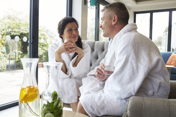 Couple Wearing Robes Relaxing On Hotel Spa Break