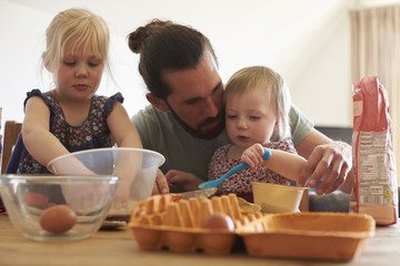 Father With Daughters At Home Baking Cakes Together