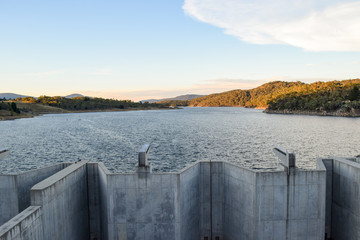 Weighted flood gates on Jindabyne Dam, Snowy River.  The surrounding mountain landscape and cloudscape.  Lake Jindabyne is part of the ground breaking 'Snowy Mountains Hydro-Electric Scheme'.