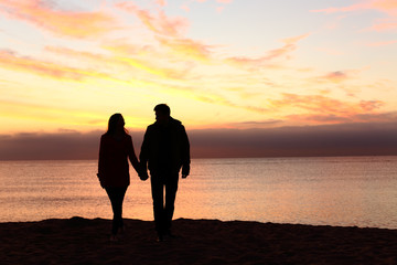 Couple silhouettes walking together at sunset