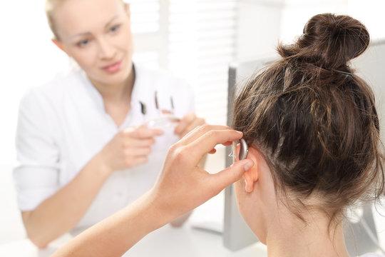 Lekarz laryngolog tłumaczy dziecku jak nosić aparat słuchowy