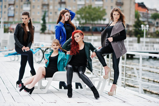 Five beautiful young girls models at leather jackets posing on b
