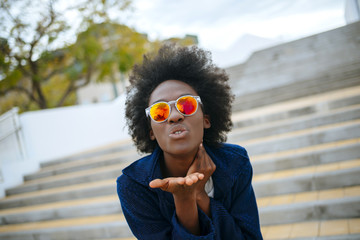 Portrait of young woman wearing mirrored sunglasses throwing a kiss to camera
