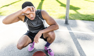 Basketball player crouching on outdoor court