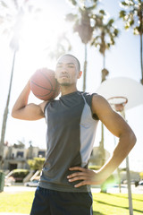 Portrait of self-confident basketball player on outdoor court
