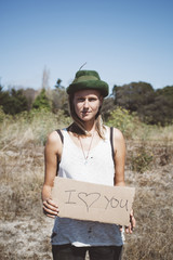 Hippie holding 'I love you' sign in the nature