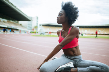 Young black athlete stretching before race in stadium