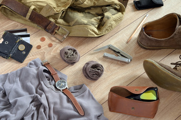 Sand-colored clothes and accessories lie on the wooden floor.