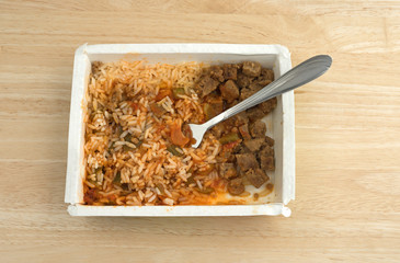 Rice peppers and beef chunks in paper tray with fork