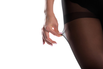 female legs in black nylon pantyhose on white background.