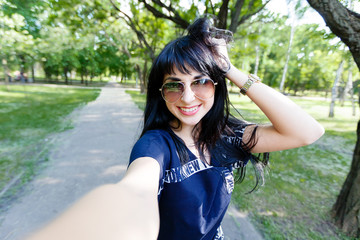 Smiling brunette woman makes selfie photos looking to camera