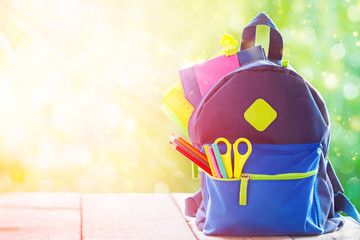 Full School backpack on wooden and nature background.