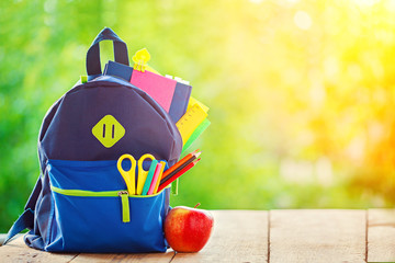 Full School backpack with apple on wooden and nature background.