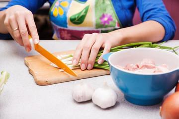woman cuts green onions