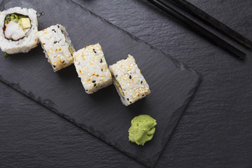 Sushi roll with ginger wasabi and soy sauce on a stone plate over black background