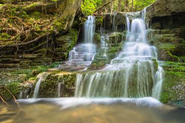 waterfall between mossy rocks. beautiful forest stream