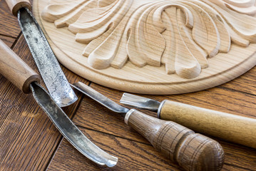 timber processing. Joinery work. wood carving. a wood carvings, tools on the wooden background close up. blurred. used as background