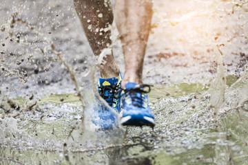 Trail runner man walking in a puddle, splashing his shoes