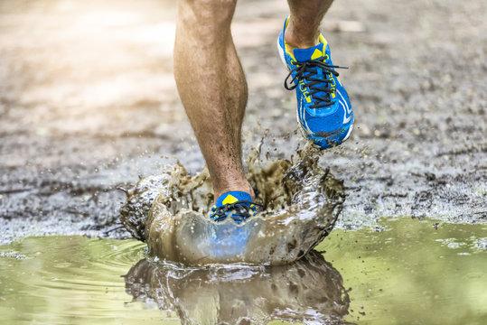 Running man walking in a puddle, splashing his shoes. Cross