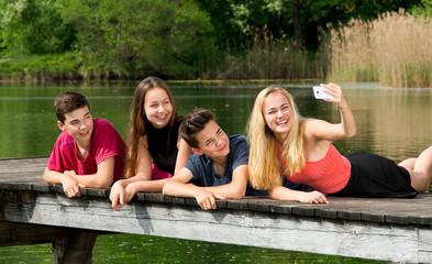Gruppe Jugendliche / Teenager machen draußen ein Selfie