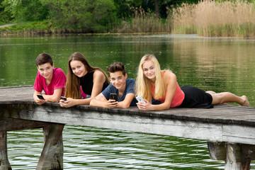 Gruppe Jugendliche liegen mit Smartphone draußen am See