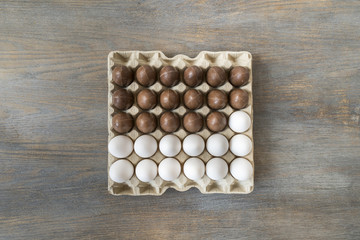 Chocolate and white boiled eggs in a recycled paper tray